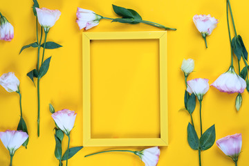 Empty yellow frame and flowers eustoma as layer on yellow paper background with copy space. Holiday concept