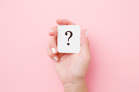 Card of question mark in young woman hand on pastel pink background. Concept of plans, thoughts or other good ideas for making decision. Closeup.