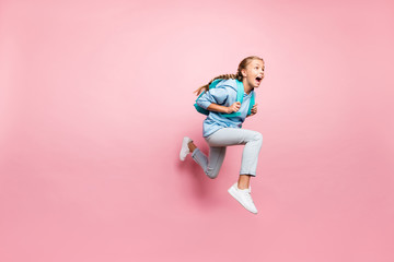 Full length body size turned photo of frightened fearful girl running away in fear with backpack behind wearing blue sporty wear sweatshirt jeand denim hoodie isolated over pink pastel color