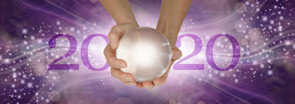 Experience a Crystal Ball Reading - What does 2020 hold for you - female hands holding a large clear crystal ball between 20 and 20 making 2020 against a wide purple sparkling flowing background