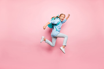Full length body size photo of cheerful excited crazy positive girl running fast with rucksack behind her back wearing blue sweater jeans denim isolated over pink pastel color background