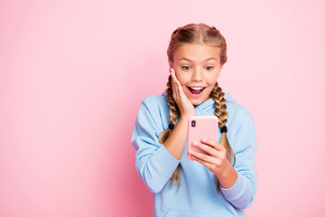 Photo of casual positive nice cute trendy stylish crazy excited schoolgirl wearing sweater sport wear holding telephone reading feednews expressing positive emotions isolated over pastel color