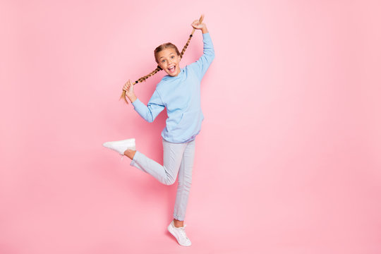 Full length body size turned photo of cheerful trendy casual screaming cute schoolgirl wearing jeans denim ecstatic about sales started at child shop nearby isolated over pink pastel color background