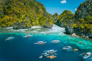 Aerial view of tourist boats in front of big Lagoon at Miniloc Island, El Nido, Palawan, Philippines. Surreal karst limestone ridge formation
