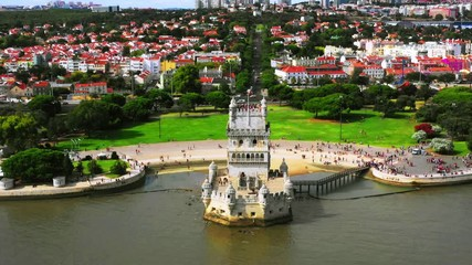 Wall Mural - Lisbon, Portugal. Aerial view of Belem Tower in Lisbon, Portugal during the cloudy day. Famous buildings with crowd of tourists, zoom out