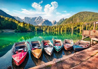 Six pleasure boats on Fusine lake. Bright morning scene of Julian Alps with Mangart peak on background, Province of Udine, Italy, Europe. Traveling concept background.