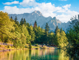 Sunny morning view of Fusine lake. Colorful summer scene of Julian Alps with Mangart peak on background, Province of Udine, Italy, Europe. Traveling concept background.