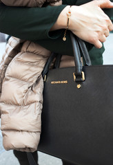 SORRENTO, ITALY - APRIL, 19, 2015: Close up of a bag Michael Kors while a young woman walking in the town center.