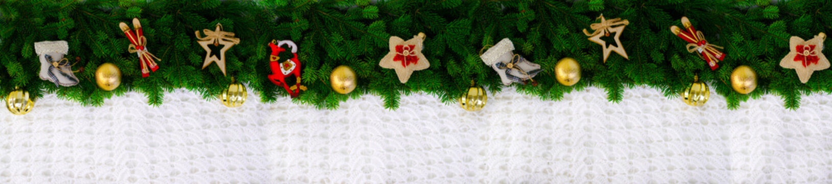 Christmas long banner made of fir branches with decorative wooden and textile toys, as well as golden balls. Knitted jersey. Top view, flat lay. Copy space