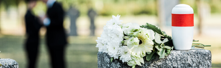 panoramic shot of white flowers and cemetery urn on tombstone