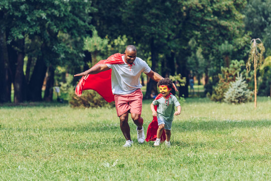 happy african american father and son running in costumes of superheroes in park