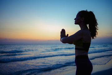 young woman on seacoast in evening doing yoga