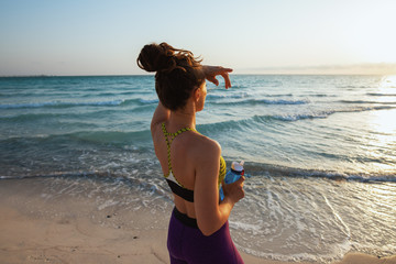 healthy sports woman with water on seashore in evening