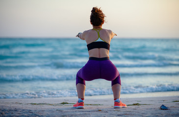 fitness woman on ocean coast in evening doing squats