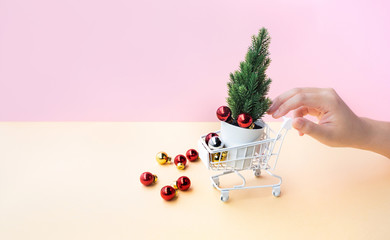 Young woman hand pushing mock up cart,trolley and christmas ornament in side,over all on pastel color background