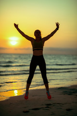 young sports woman on seashore in evening training