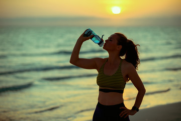 fit woman on beach at sunset drinking water from bottle