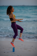 young woman on seacoast in evening workout
