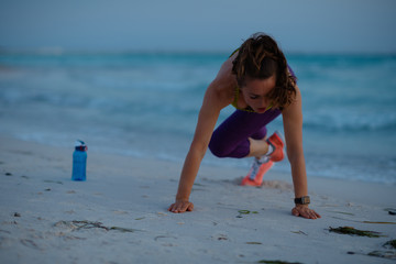 healthy sports woman on ocean coast in evening workout