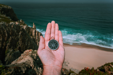 Looking at the compass in man hand palm symbolling adventure-seeking concept against sea and waves in coastline in background