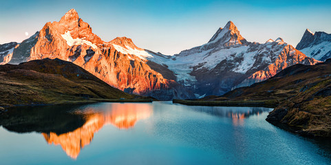 Fotobehang Alpen Breathtaking evening panorama of Bachalp lake/Bachalpsee, Switzerland. Exciting autumn sunset in Swiss alps, Grindelwald, Bernese Oberland, Europe. Beauty of nature concept background.