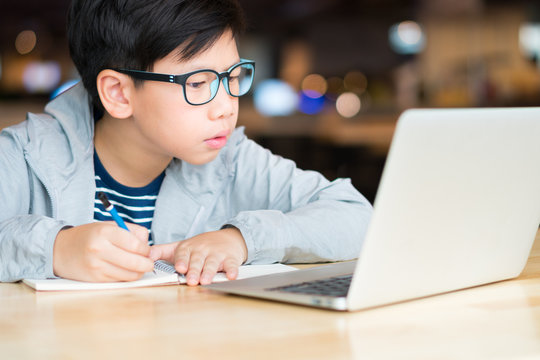 Smart looking Asian preteen boy writing and using computer laptop studying online lessons. Researching, studying and solving problem with concentration. Online learning and self study concept.