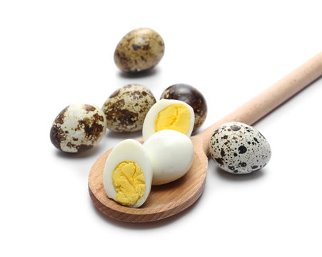 Boiled quail eggs and wooden spoon isolated on white background