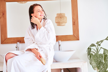 Photo of happy brunette girl with comb and wet hair sitting in bath in apartment