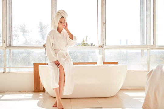 Picture of girl looking at side in white bathrobe and with towel on her head standing near bath in room with large window