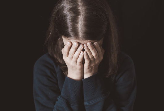 Portrait of a crying woman covering her face with hands on a black background. Violence in family. Sadness and depressive state of the girl.