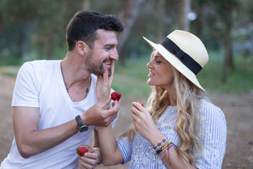 Young couple feeding each other on picnic with strawberry