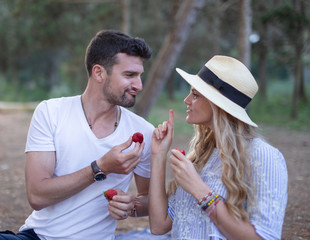 Happy young couple joking during picnic in nature
