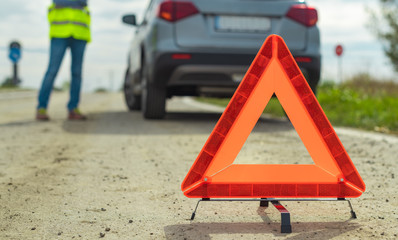 Vehicle breakdown and warning triangle on the road
