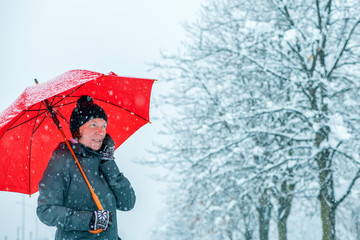 Satisfied woman talking on mobile phone under umbrella in snow
