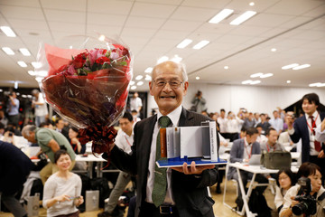 Asahi Kasei honorary fellow Akira Yoshino, 2019 Nobel Prize in Chemistry winner, holds a mock of lithium-ion battery and a flower bouquet during a news conference in Tokyo