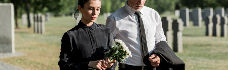 panoramic shot of bearded senior man near woman with flowers on funeral