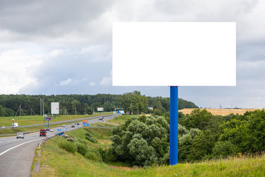 White blank panel mock-up along highway against fields