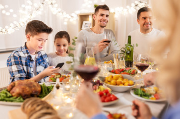 technology, holidays and people concept - happy children with smartphone at family dinner party
