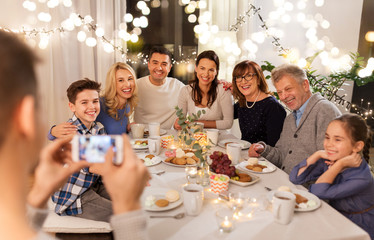 celebration, holidays and people concept - happy family having dinner party at home and taking...