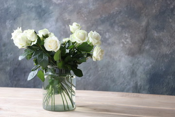 a bouquet of white roses in a glass vase in a room with a concrete gray wall