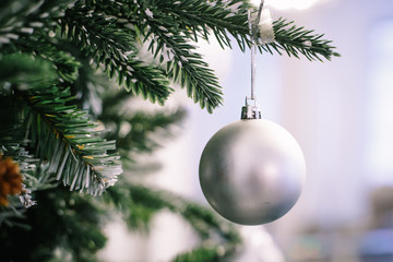Christmas tree branch decorated with silver balls and white decor
