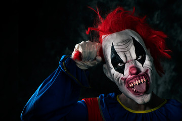 scary evil clown sticking out his tongue