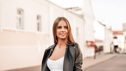 Portrait of a beautiful pretty young woman with a cute smile with natural make-up with brown hair in a stylish black leather jacket in a white elegant top. Attractive happy girl walks on a city street