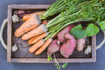 Sweet potato and carrots in a wooden box.