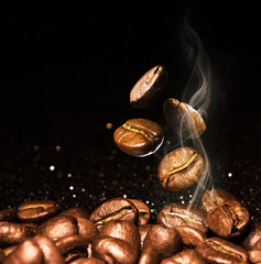 Canvas Prints Cafe Roasted coffee beans. Seeds of freshly roasted coffee with smoke. Coffee beans closeup with emphasis on the grain with smoke.