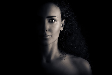 Beautiful young woman with curly hair looking sexy with half shadow on the face. Closeup portrait. Black and white Photography.