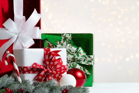 Christmas white, green and red gift boxes with assorted ribbons by some snowy fir or pine branches with cones and red berries over a bright light background with natural bokeh and copy space.