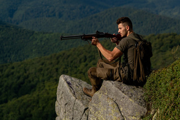 Track down. Hunting Gear - Hunting Supplies and Equipment. Hunter with a shotgun in a traditional...