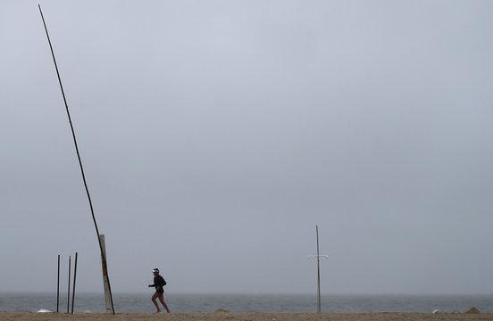 Man runs during a rainy day on Copacabana beach in Rio de Janeiro