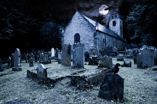 old graveyard with ancient tombstones grave stone and old church front of full moon black raven dark night spooky horror background